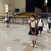 masked students in socially distanced lines go back to school during the COVID-19 pandemic