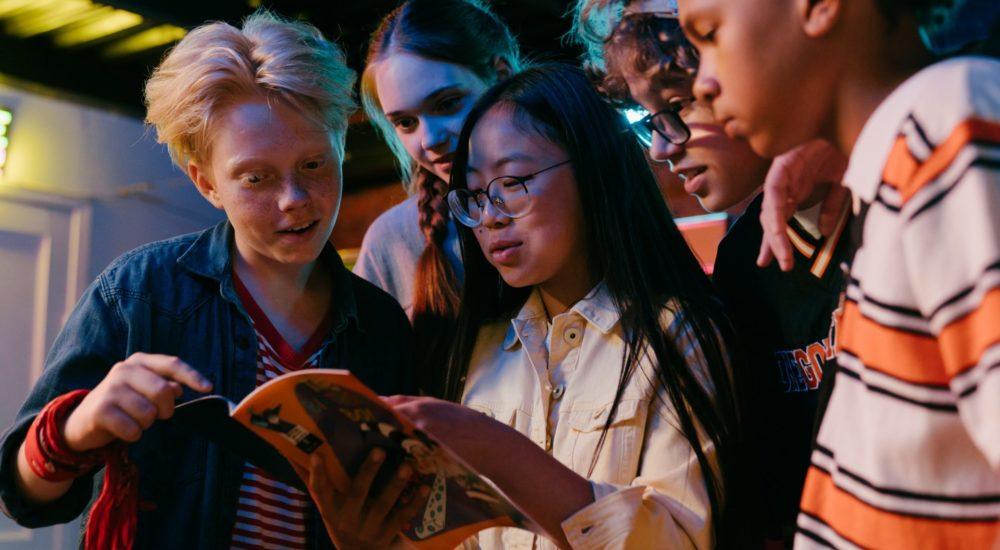 youth gathered together looking at a comic book