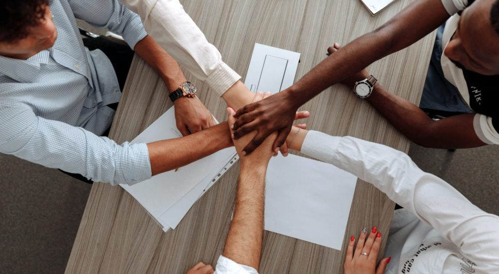 5 team members put their hands in the center for support