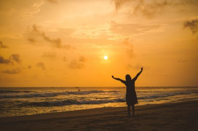 silhouette of woman with arms raised overhead against an orange sky during sunrise