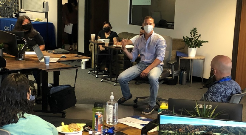 man in mask leading staff meeting